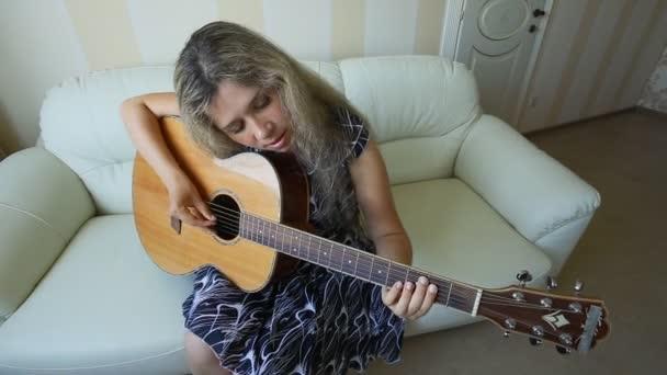 dívka s kytarou doma