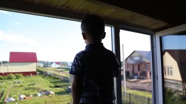 blonďaté dítě sedí u okna a díval na kapky, uvnitř