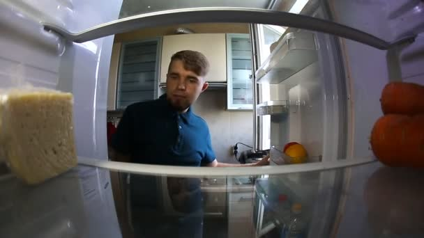 muž hledá uvnitř lednice