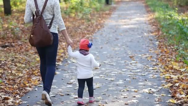 Mutter und kleine Tochter spazieren im Herbst