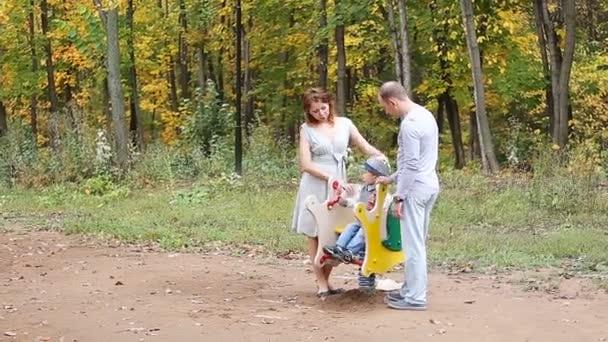Táta máma a dítě hraje na hřišti