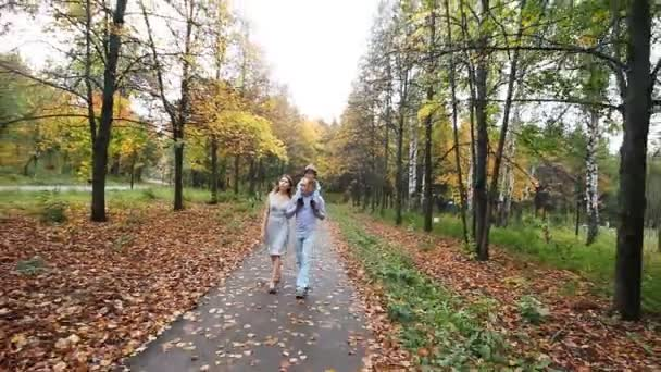Happy smiling family walk in autumn park