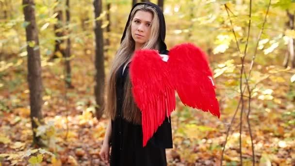 Krásná dívka s červenými andělská křídla v lese