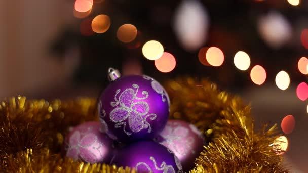 Tři fialové vánoční koule na světlém pozadí bokeh