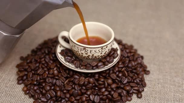 eine Tasse Kaffee mit Kaffeebohnen einschenken