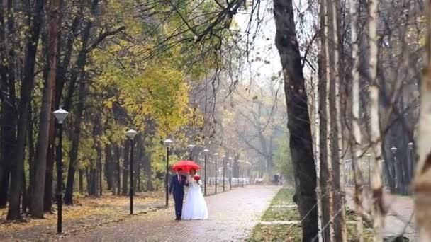 Wedding couple holding red umbrella
