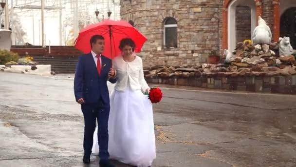 Hochzeitspaar mit rotem Regenschirm