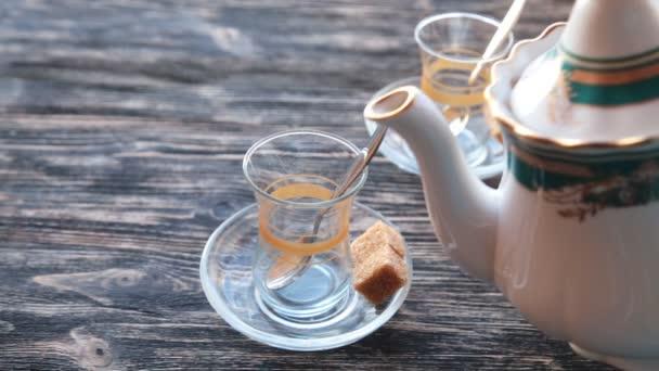 Nalévání čaje do hrnku na dřevěný stůl