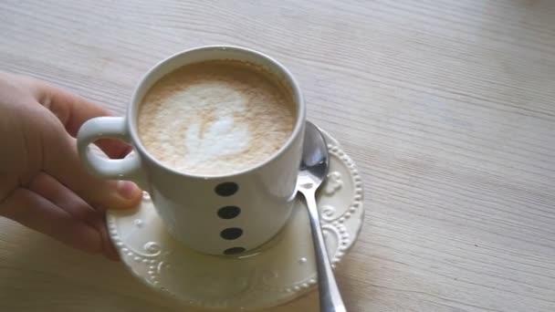 Egy ember teszi egy csésze kávé az asztalra slowmotion