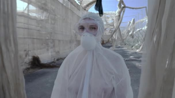 Problem of a coronavirus COVID-19 Female Research Scientist in hazmat outfit walking through the Apocalyptic space a Wuhan Pandemic of the Planet. Dead space