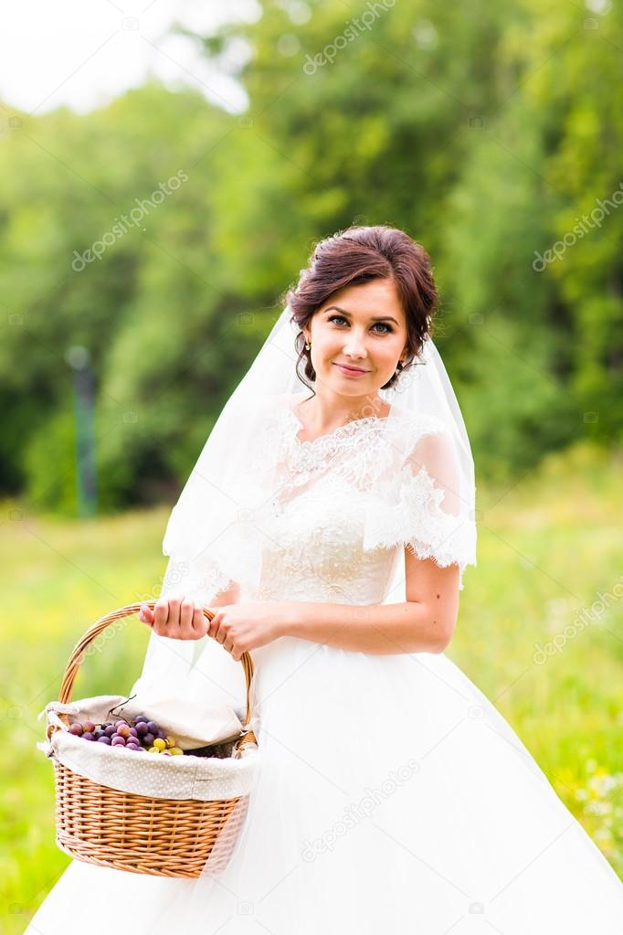 Beauty bride in bridal gown with basket on the nature. Beautiful ...