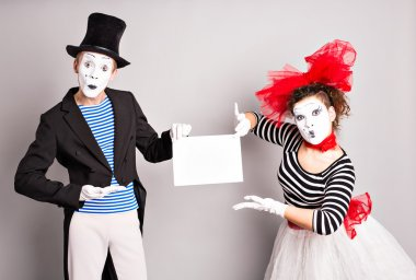 Your text here. Actors mimes holding empty blank board. Colorful studio portrait with gray background. April fools day