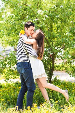 Loving couple under blossoming branches spring day. Young adult  brunette man and woman kissing in fresh blossom apple or cherry trees garden. sweet kiss