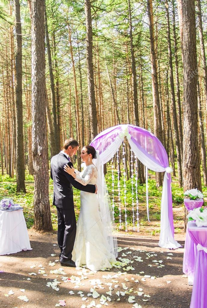 wonderful stylish rich happy bride and groom dancing at a wedding ceremony in green garden near purple arch with flowers