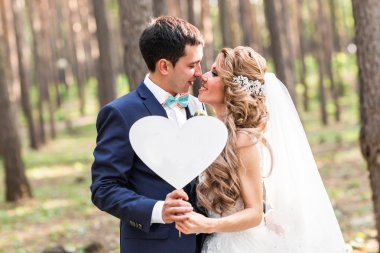 happy Groom and Bride in a park with sign as heart