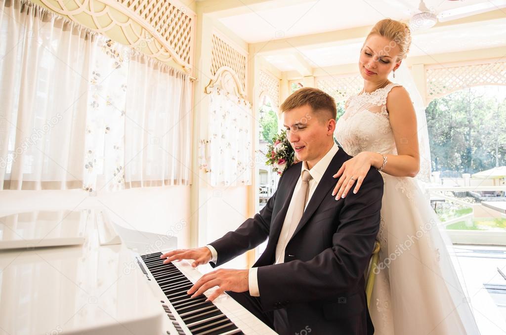 Para ślub Gry Na Fortepianie W Pokoju Zdjęcie Stockowe Satura