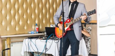 Young man playing on electric guitar