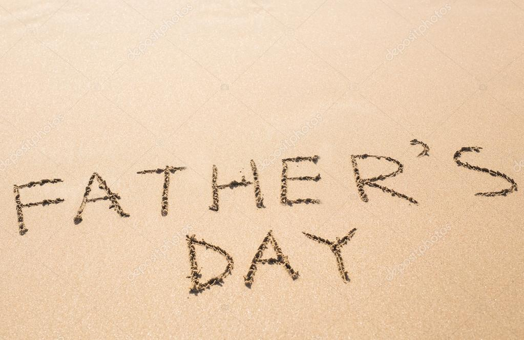 Fathers Day hand written in the sandy beach