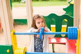 Fotografie Kleines Mädchen auf einem Spielplatz. Kinder spielen im Freien im Sommer