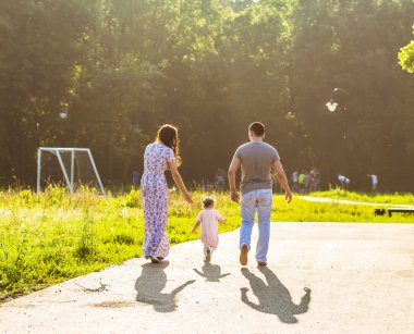 Happy Young Family Walking In The Park.