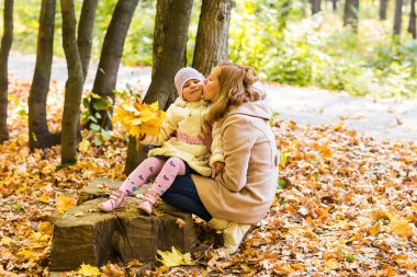 Mother kissing her daughter in the park.  Woman with child on autumn forest.