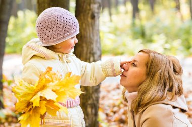 Happy family mother and  little daughter playing on autumn walk