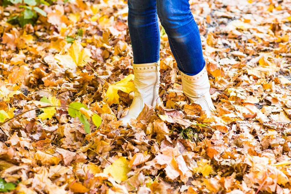 legs in boots on the autumn leaves. Feet shoes