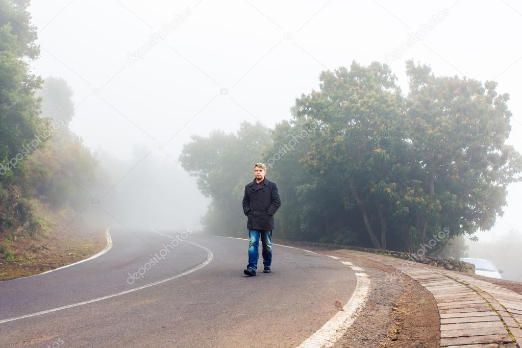 Man walking in a misty forest