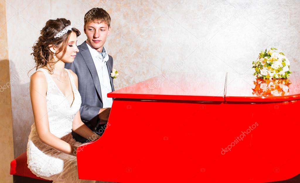 Uroczy Para ślub Gry Na Czerwony Fortepian W Pokoju Zdjęcie