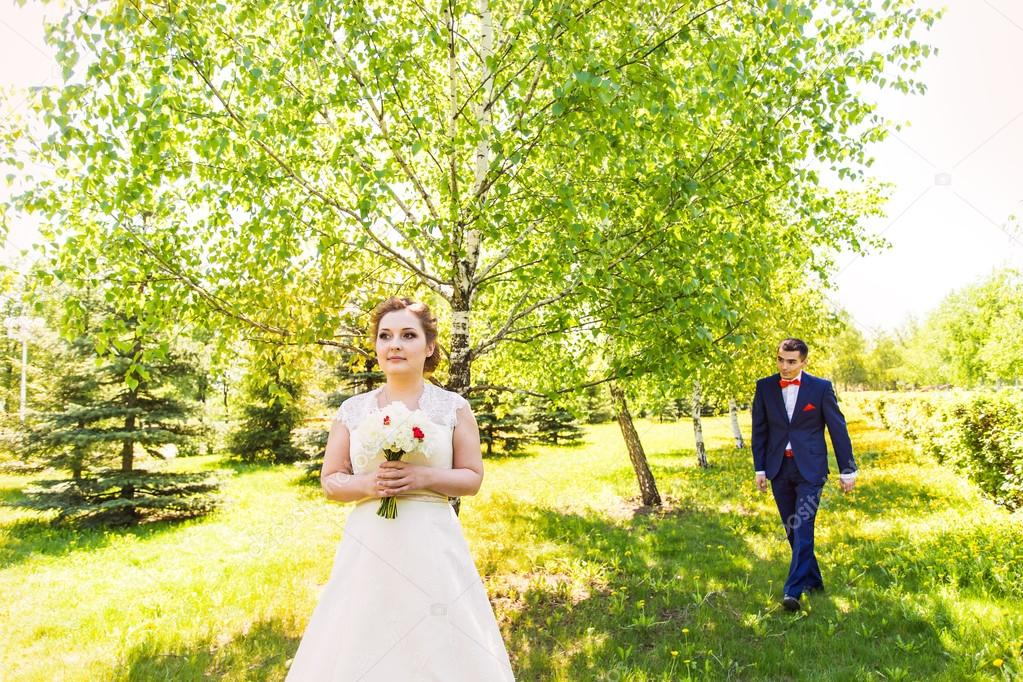 couple in wedding attire with a bouquet of flowers and greenery is in the hands against the backdrop of the garden, the bride and groom