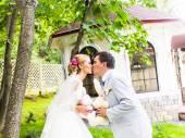 Paar in Hochzeit Kleidung mit einem Strauß Blumen und grün ist in den Händen, die Braut und Bräutigam küssen