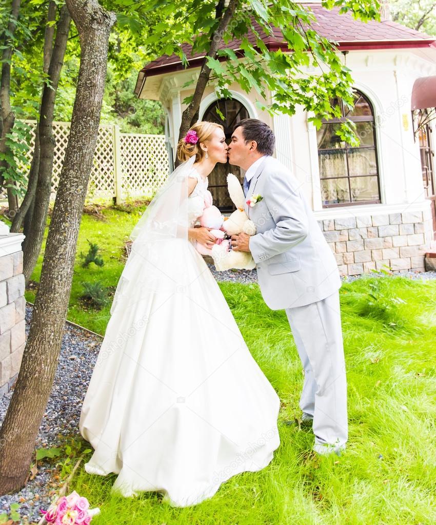 Paar in Hochzeit Kleidung mit einem Strauß Blumen und grün ist in ...