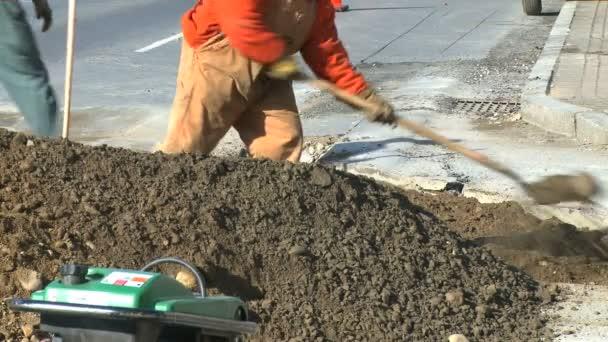 Muži používají lopaty a zařízení na staveništi