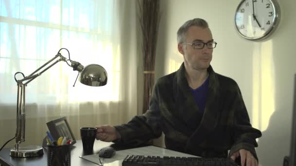 A man works at a clean desk with a computer and keyboard