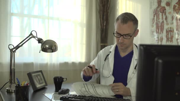 A doctor works at his office desk