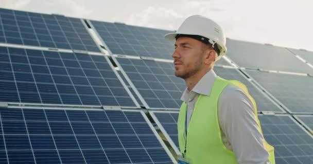 Seitenansicht eines gut aussehenden männlichen Ingenieurs in Uniform, der ein Solarkraftwerk betrachtet. Mann mit Helm untersucht Objekt, während er Schriftrollen der Zeichnung trägt. Konzept der grünen Energie.