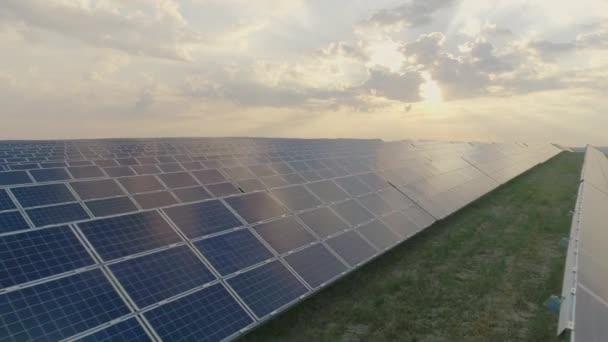 Drone kilátás alternatív napenergia farm panelek álló sorokban mező gyönyörű felhős ég. A zöld megújuló energia koncepciója és a jövőbeli innovációk.