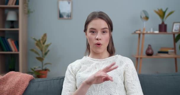 Crop kilátás fiatal nő mutatja süket-néma jelbeszéd megy vegán és a kamerába. Csinos női személy támogatja a vegetarianizmust, miközben otthon ül a kanapén.