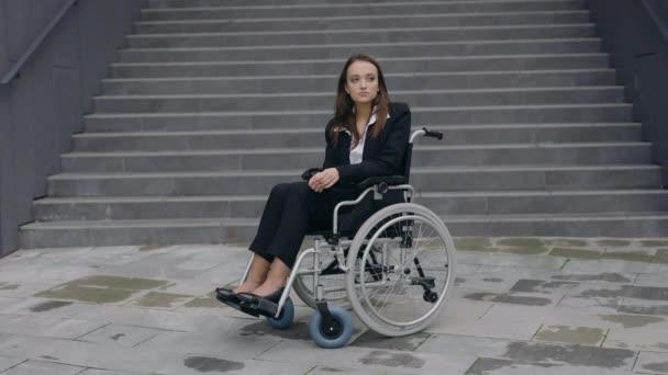Porträt einer behinderten jungen Frau im Anzug, die im Rollstuhl in der Nähe der Treppe eines Bürogebäudes sitzt. Behinderte attraktive Frau schaut im Freien zur Seite.