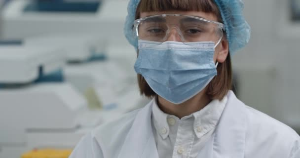 Schnittansicht einer Frau in Schutzmaske und Brille, die den Kopf dreht und in die Kamera blickt. Kopfschuss einer Ärztin in weißem Mantel und Bouffant-Mütze im Labor. Forschungskonzept.