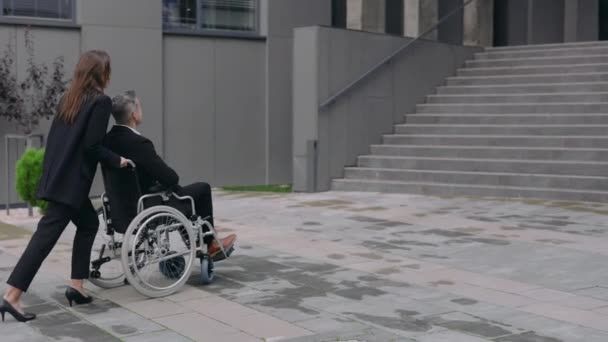 Stilvolle Frau im Anzug schiebt Rollstuhl mit männlichem Kollegen und bleibt vor der Treppe des Bürogebäudes stehen. Weibliche und behinderte männliche Geschäftsleute auf dem Weg zur Arbeit. Konzept der Unterstützung und Hilfe.