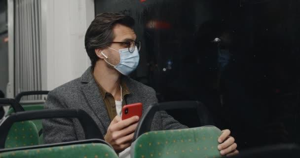 Schnittansicht des Mannes mit medizinischer Maske und Brille mittels Smartphone. Männliche Person mit Ohrhörern, die zum Fenster schaut, während sie in sozialen Medien plaudert und in öffentlichen Verkehrsmitteln sitzt. Pandemiekonzept.