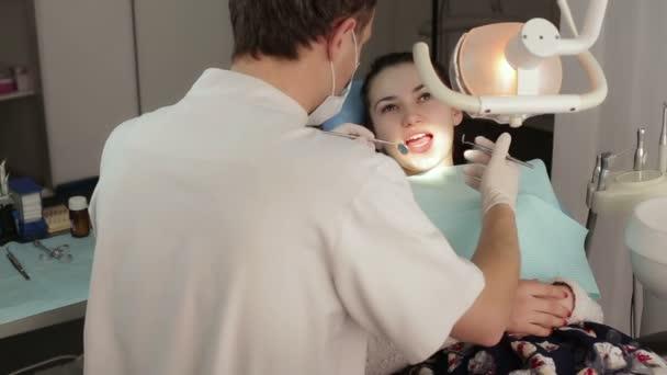 Zahnarzt untersucht Zähne einer Patientin