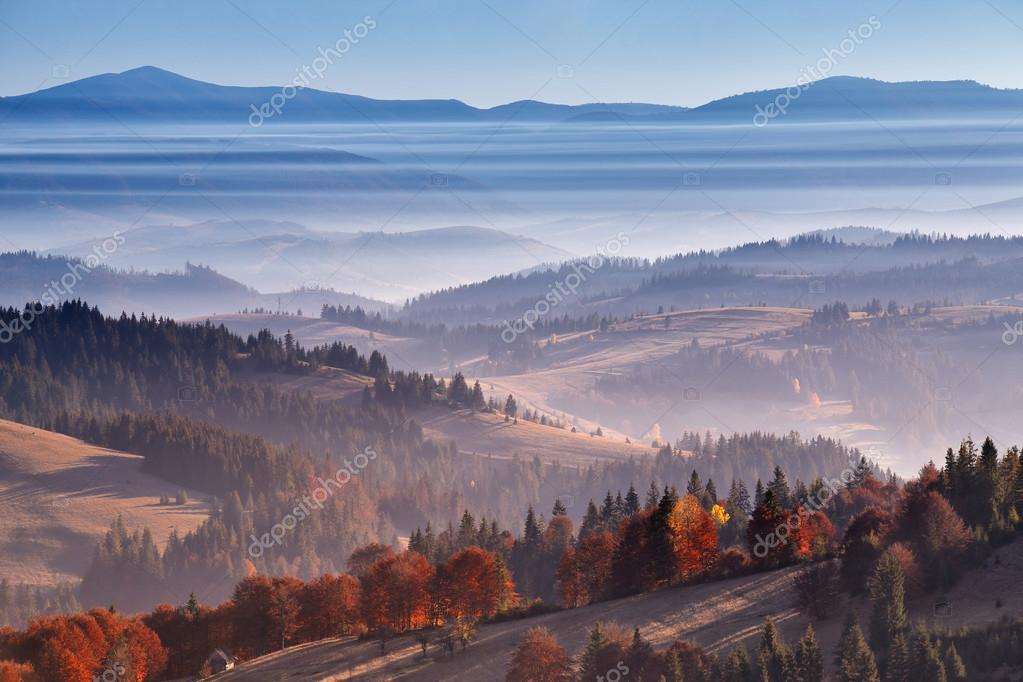 Morning mist in mountains. Sunrise and autumn mist over the hill