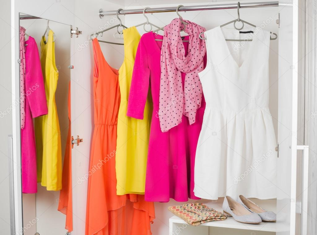 Colorful dresses hanging in long closet
