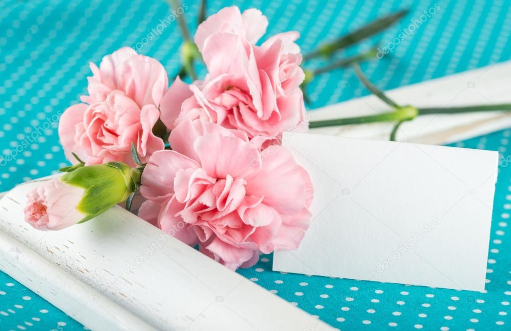 Greeting card with pink carnations on a bright blue background w