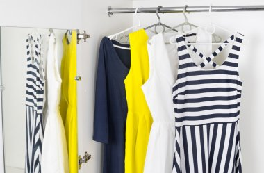 Modern fashion womens dresses on hangers in a white cupboard