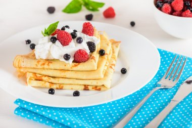 Delicious sweet crepes decorated air-cream and ripe berries