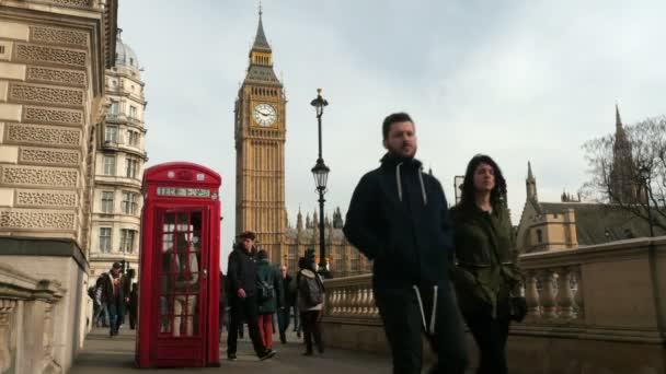 Pěší chůze a dopravní provoz procházející londýnským červeným telefonním polem nedaleko Big Ben