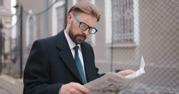 Muž v obleku čtení novin venku